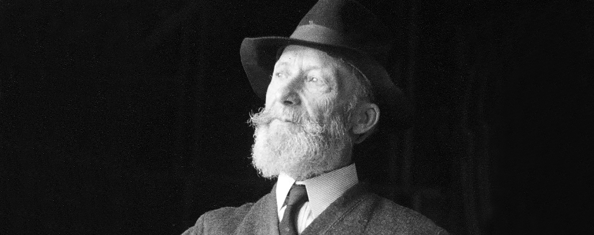 Black and white photograph of Ozias Leduc, sitting, aged 70 to 75. He wears a hat and has a beard. He has his left hand in his trouser pocket.