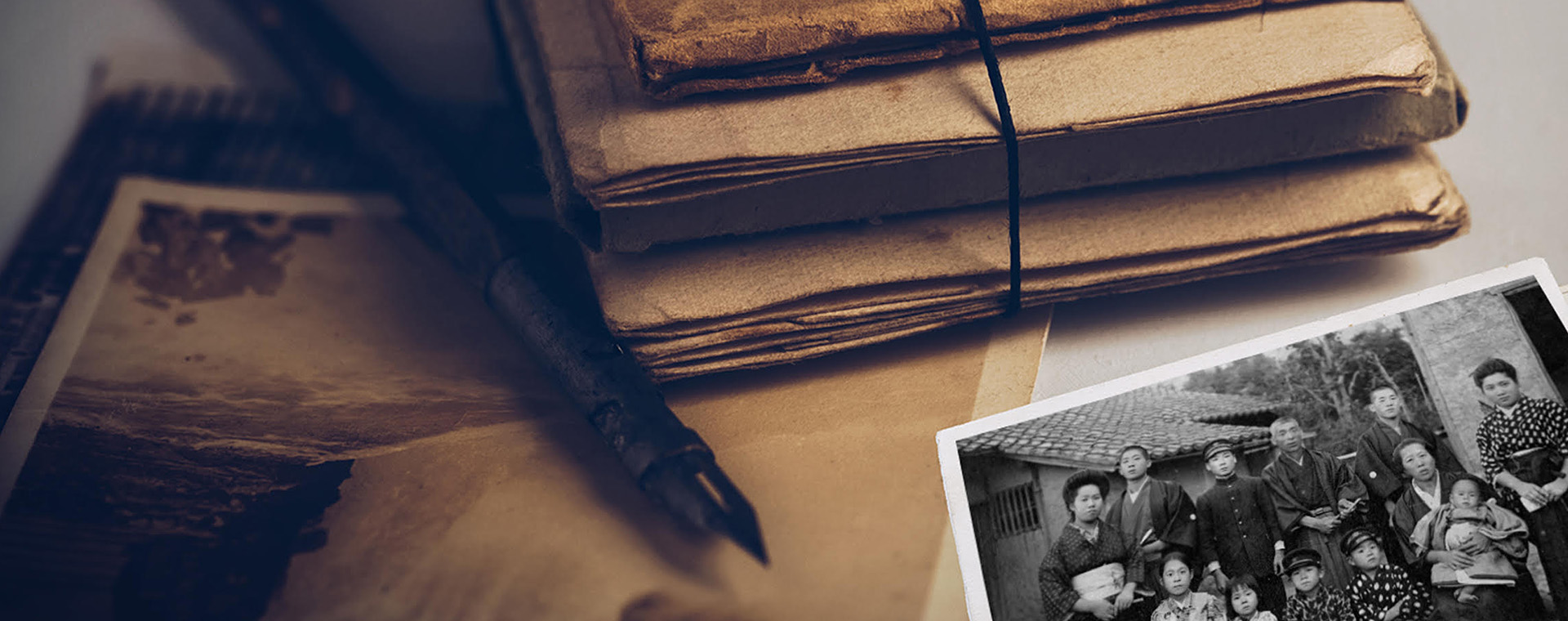 A bundle of sepia-toned documents on a desktop surface with a sepia-toned album and black-and-white photo of people